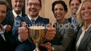 Happy lawyers holding trophy