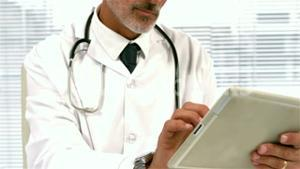 Confident doctor using tablet