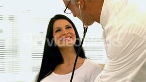 Doctor checking with stethoscope pregnant woman