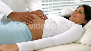 Doctor with hands on pregnant womans belly