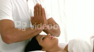 Therapist performing reiki on pregnant patient