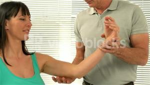 Therapist holding his patient arm