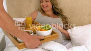 Husband with breakfast tray for happy pregnant wife