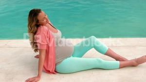 Pregnant woman sitting near the pool