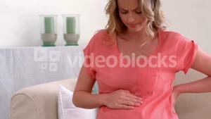 Pregnant woman with backache touching back and belly