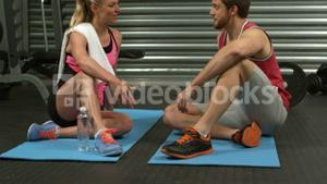Smiling fit couple sitting on mat talking at the gym