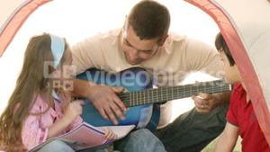 Two kids with their dad playing the guitar