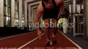 Fit man running on indoor track