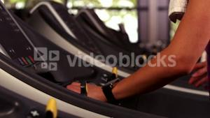 Fit woman running on the treadmill with a connected watch