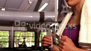 Fit woman running on the treadmill while listening music