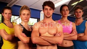 Serious fit group standing with arms crossed