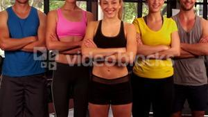 Smiling fit group standing with arms crossed