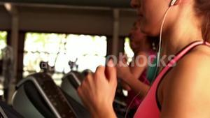 Fit woman running on treadmills while listening music