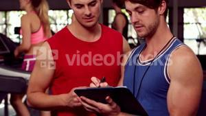 Fit male trainer speaking with a muscular man