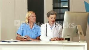 Female doctors using tablet and computer