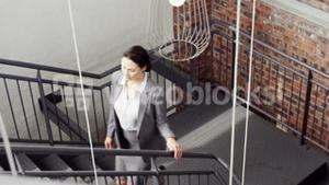 Pretty businesswoman climbing the stairs