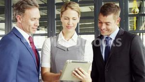 Business people talking together while looking tablet