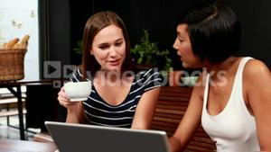 Smiling friends using laptop