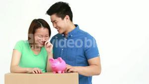 Cute couple with moving box and piggy bank
