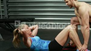 Fit woman doing sit ups with trainer
