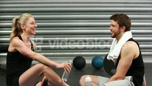 Smiling fit couple sitting on mat talking