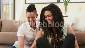 Lesbian couple using laptop while siting on the floor