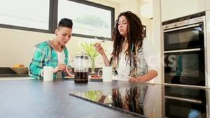 Smiling lesbian couple eating breakfast together in the kitchen