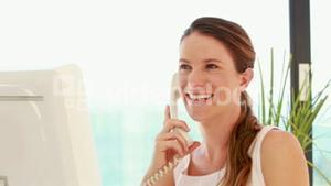 Smiling woman using computer while having a phone call