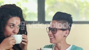 Smiling lesbian couple drinking coffee together