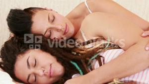 Calm lesbian couple sleeping together in the bed