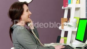 Pregnant woman using computer have a phone call