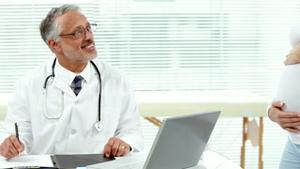 Pregnant smiling woman consulting doctor