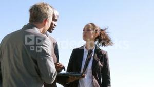 Three businesspeople having a meeting outdoors