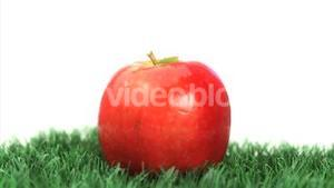 Red apple rotating on grass