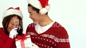 Festive Asian couple holding Christmas present and smiling