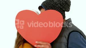 Couple hiding faces with heart shape