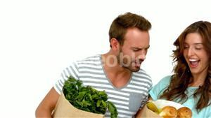 Happy couple holding grocery bags
