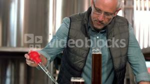 Focused brewery worker using pipette