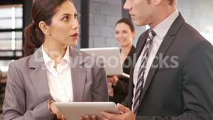 Serious business people using digital tablet