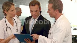 Doctors discussing the report on clipboard