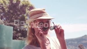 Attractive blonde with hat taking off sunglasses