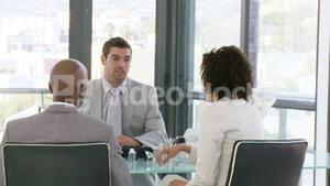 Three wealthy businesspeople talking about business