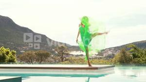 Young happy woman dancing poolside