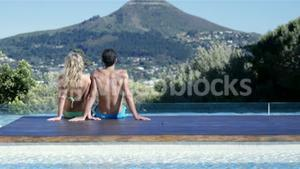 Couple sitting with feet in the pool