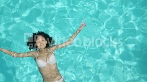 Attractive woman floating in the pool