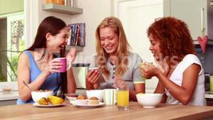 Friends laughing while eating breakfast together
