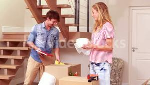 Young smiling couple unpacking boxes