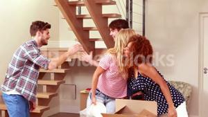 Young lovely couple unpacking boxes while visiting by friends