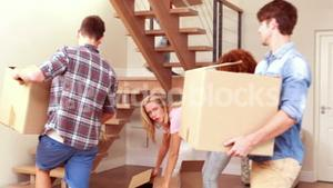 Smiling friends moving boxes together