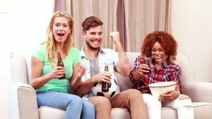 Smiling friends watching tv while eating popcorn and drinking beer